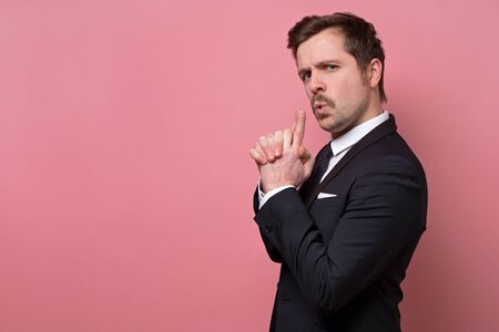 Confident young businessman makes shooting gesture like secret agent, recieves great success