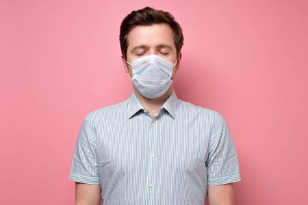 Caucasian young unemotional man wearing medical mask standing with closed eyes