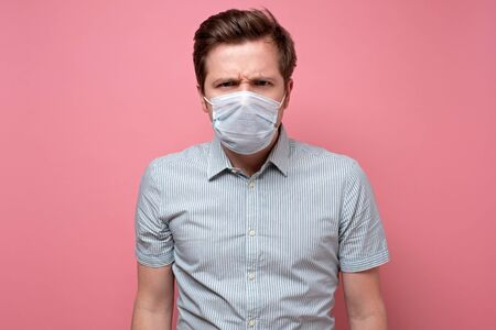 Caucasian young man wearing medical mask trying to protect from flu