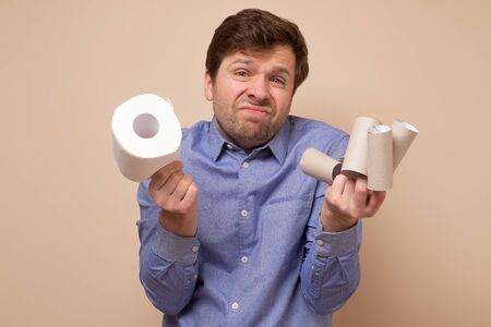 man with one toilet paper roll and empty sleeves. Panic of pandemic quarantine
