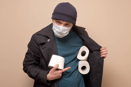 speculator man holding several roll of toilet paper.