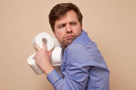 Greedy caucasian man holding several rolls of toiler paper on his hand hiding it