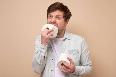 Funny caucasian young man eats a toilet paper.