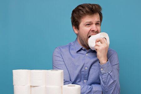 Concept of Funny caucasian young man eats a toilet paper.