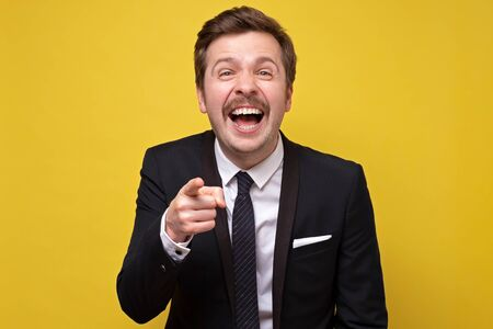 Young caucasian man mocking you or laughing on his friend joke. Studio shoot on yellow background.