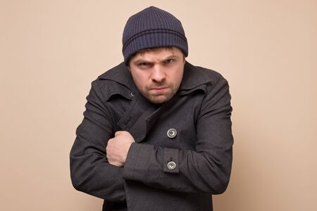 Young caucasian speculator man gangster or bandit looking angry at camera closing his coat. Studio shot