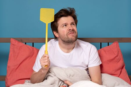 Young caucasian man holding a fly swatter wanting to kill annoying mosquito