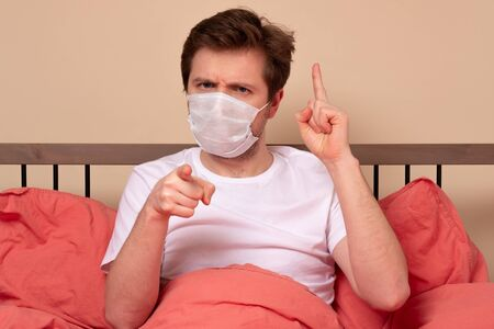 Angry man in medical mask pointing his finger at you sitting in the bed at home. Do you stay at home when you are ill.