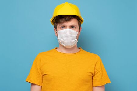 Caucasian workman wearing a yellow hard hat and medical mask during quarantine at the camera. Isolated over blue wall.