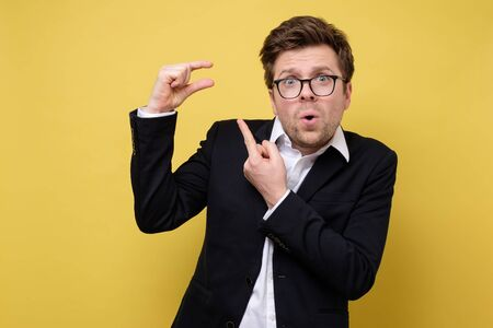 Young caucasian man gesturing with hand showing small size sign with fingers. Measure concept. Studio shot on yellow wall.