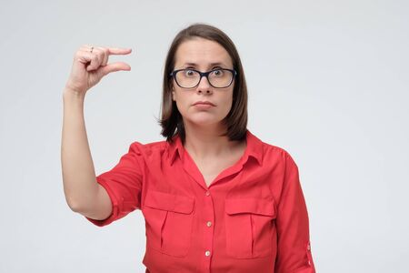 It is too small. Beautiful mature woman in red shirt gesturing small size with her fingers. Small payment or salary concept.