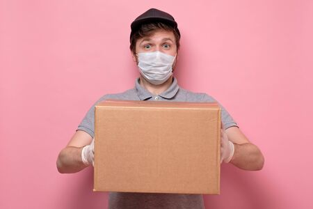 Young delivery man holding and carrying a cardbox