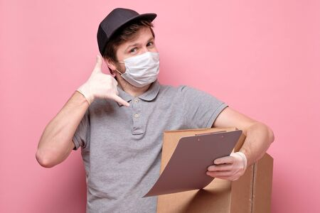 delivery man in medical mask holding a cardbox showing phone me gesture