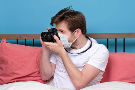Young photographer in medical mask being ill sitting on quarantine alone with camera, isolated on blue wall.