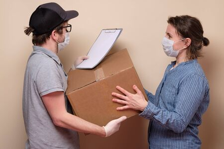 Young delivery man in medical mask giving a cardbox parcel to female client isolated on beige background