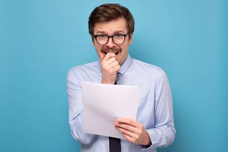 man in funny glasses holding his speech at hands reading being afraid