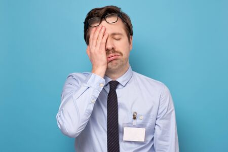 Tired and exhausted guy looking unsatisfied and tired after hard working day Stock Photo