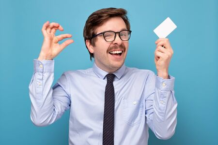 Smiling positive Caucasian man in glasses show small size by fingers hodfing a credit card, demonstrate tiny measure, tell about little decreased prices or interest rate