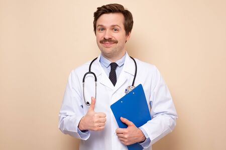 Successful doctor man giving thumbs up approving your choice