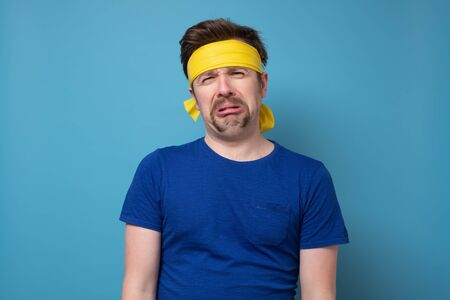 Young caucasian sport man with yellow rubber band whining and crying Standard-Bild