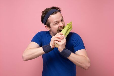 Sportive caucasian young man with celery on pink background. I love vegetables so much. Green diet concept.