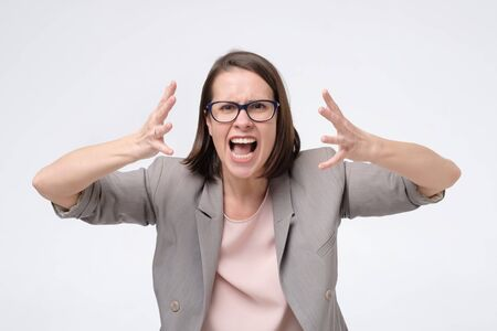 Screaming, hate, rage. Crying emotional angry woman screaming on white studio background. Human negative emotions, facial expression concept.