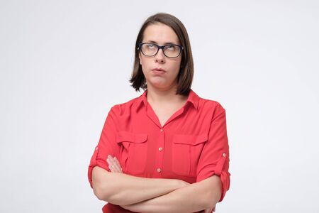 Upset woman in glases and red clothed pouting and looking offended isolated over white background in studio