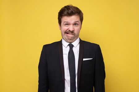 Portrait of a pensive young man with funny mustache in suit against a yellow background Stock Photo