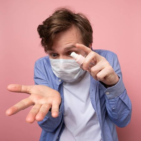 Coronavirus protection and disinfection or OCD concept. Caucasian man in medical mask spraying sanitizer spray on his hand over pink background