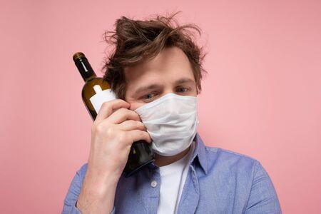 Sad caucasian man in medical mask complaining and drinking wine alone. Studio shot