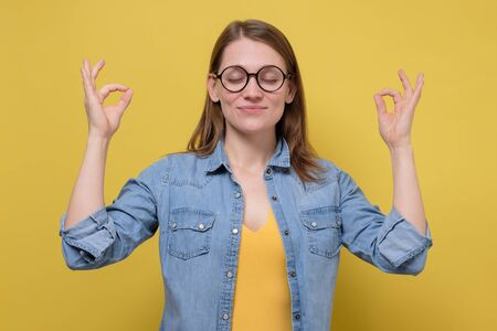 Beautiful woman in glasses in meditation on yellow wall