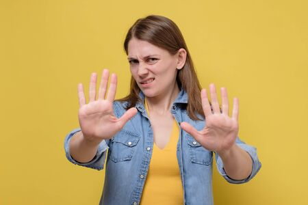 Young woman wearing casual clothes standing over yellow background moving away hands. Zdjęcie Seryjne