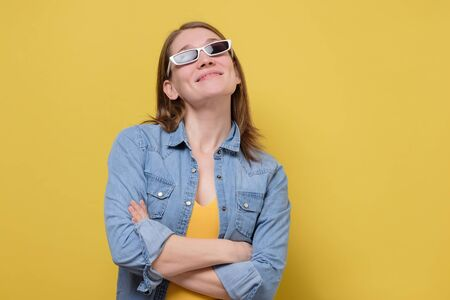 Young woman wearing retro sunglasses in denim clothes on yellow wall