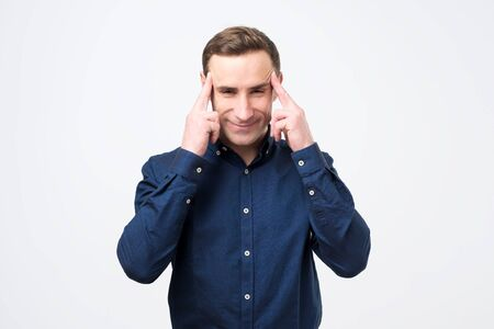 Young caucasian male keeps fingers on temples, selects best suitable solution in life. Studio shot Stock Photo
