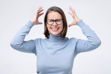 Shocked angry scared young woman screaming holding hands near face arguing with her husband isolated on white background.