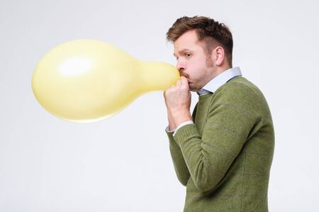 young man in green sweater inflating yellow balloon. Test on lungs strength.