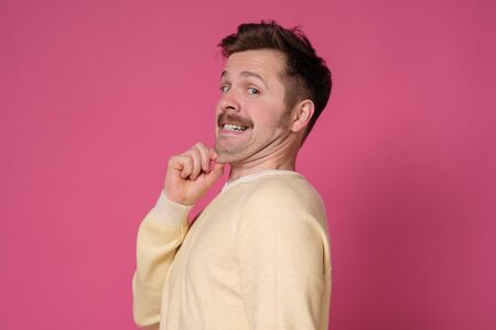 Young man in yellow shirt with a double chin. Overweight as a result of improper diet. Studio shot on pink wall.