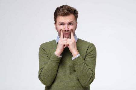 European man keeps fingers on cheeks, tries to make himself smile being stressed. He lost his job but try not to cry. Studio shot