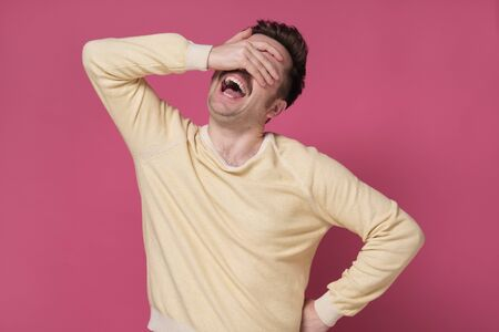 Handsome man laughing with hand on face covering eyes for surprise. Blind concept. Studio shot