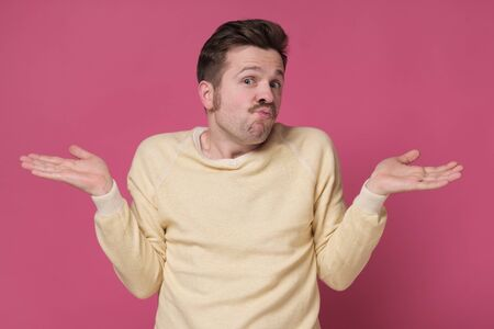Confused caucasian man is unsure having no idea what to do next, isolated on pink background. Zdjęcie Seryjne