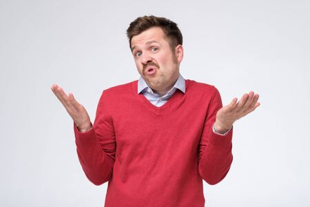 Confused caucasian man is unsure having no idea what to do next, isolated on white background.