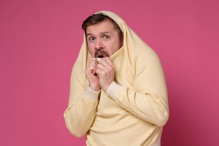 Young man wearing sweater on head looking stressed and nervous with hands near mouth. Studio shot on pink wall.