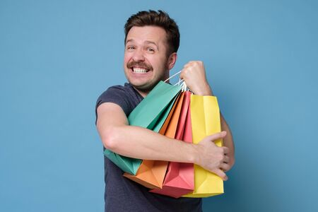 Happy caucasian man shopper holding several colored shopping bag over blue background