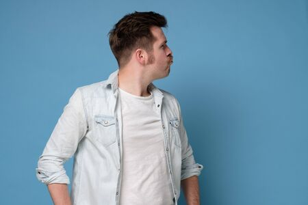 Puzzled young caucasian man in side view. Studio shot on blue wall.