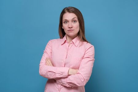 Young caucasian businesswoman with folded hands against blue background Zdjęcie Seryjne