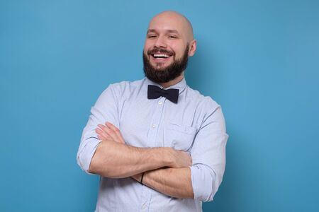 Casual caucasian man with beard standing with arms crossed smiling at camera