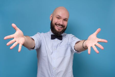 Happy casual man showing greeting gesture isolated on a blue background Zdjęcie Seryjne