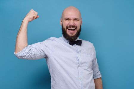 Excited happy man holding fists up being glad with his success