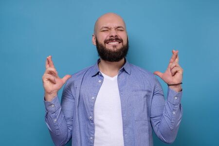 Glad positive bearded man crosses fingers, closes eyes with pleasure isolated on blue background.