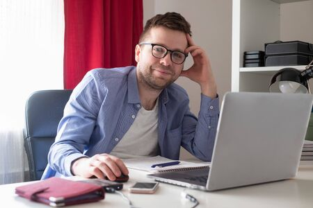 Caucasian mature man in glasses working on laptop computer from home Zdjęcie Seryjne